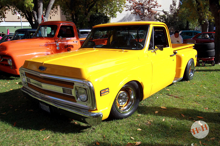 A row of classic GM trucks, featuring an orange and yellow pair of classics